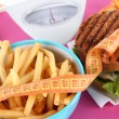 Royalty-Free Stock Photo: Hot-dog, hamburger and fries on scales close-up