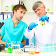 Physician and assayer during research on room background — Stock Photo #23656269