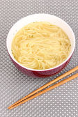 Asian noodles in bowl on grey mat — Stock Photo