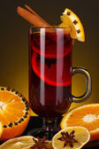 Fragrant mulled wine in glass with spices and oranges around on yellow background — Foto Stock