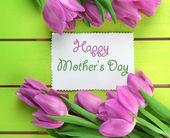 Hermoso ramo de tulipanes morados y tarjeta sobre fondo de madera verde — Foto de Stock