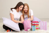 Two girl friends out gifts on room — Stock Photo