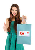 Young beautiful girl in green dress holding bright shopping bags, isolated on white — Stockfoto