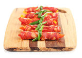 Salami rolls on wooden board, isolated on white — Stock Photo