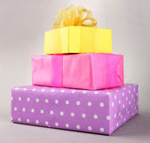 Bright gifts with bows on grey background — ストック写真