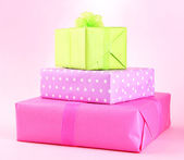 Bright gifts with bows on pink background — Stockfoto