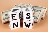 """White paper cubes labeled """"News"""" with money on beige background — Stock Photo"""