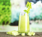 Glass of celery juice, on bamboo mat, on green background — Stock Photo