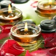 Spa stones with rose petals and candles in water on plate — Stock Photo #23811835
