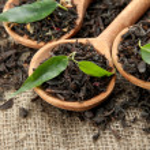 chá seco com folhas verdes em colheres de madeira, sobre fundo de serapilheira — Foto Stock
