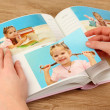Photos in hands and photo album on wooden table — Stock Photo #23812989
