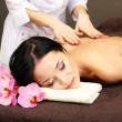Beautiful young woman in spa salon getting massage with spa stones, on dark background — Stock Photo