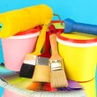 Set for painting: paint pots, brushes, paint-roller, palette of colors on blue background — Stock Photo #23813343
