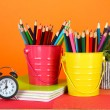 Colorful pencils in two pails with copybooks on table on orange background — Stock Photo #23814297
