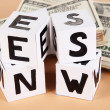 "White paper cubes labeled ""News"" with money on beige background - Foto Stock"