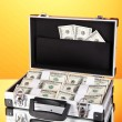 Suitcase with 100 dollar bills on orange background — Stock Photo