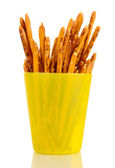 Tasty crispy sticks in yellow plastic cup isolated on white — Stock Photo