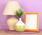 Colorful photo frame, lamp and flowers on wooden table on lilac polka dots background — Stock Photo