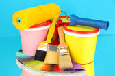 Set for painting: paint pots, brushes, paint-roller, palette of colors on blue background — Stock Photo