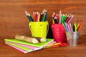 Colorful pencils with school supplies on wooden background — Stock Photo
