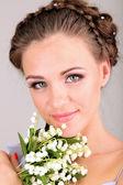 молодая женщина с красивой прической и цветы, на сером фоне — Стоковое фото