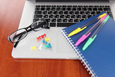 Laptop with stationery on table — Stockfoto