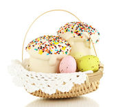 Easter cakes with eggs in wicker basket isolated on white — Stock Photo