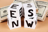 "White paper cubes labeled ""News"" with money on beige background — ストック写真"