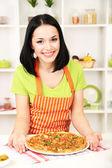 Femme au foyer de jeune fille avec délicieuses pizzas sur fond de cuisine — Photo
