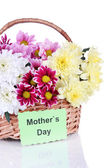 Bouquet of beautiful chrysanthemums in wicker basket isolated on white — Stock Photo