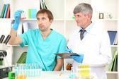 Medico e saggiatore durante le ricerche su sfondo camera — Foto Stock