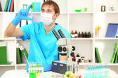 Assayer during research on room background — Stock Photo