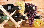 Butelki wina na drewniany stojak na tle kamiennego muru — Zdjęcie stockowe