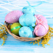 Easter eggs in basket and mimosa flowers, on blue wooden background — Stock Photo #23855991