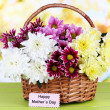 Bouquet of beautiful chrysanthemums in wicker basket on table on bright background — Stock Photo #23856053