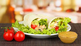 Kebab - grilled meat and vegetables, on plate, on wooden table, on bright background — Stock Photo