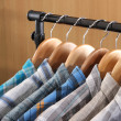 Men&#039;s shirts on hangers in wardrobe - Stock Photo