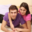 Stock Photo: Young couple lying on carpet at home
