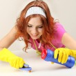 Young housewife cleaning up table at home on grey background — Stock Photo #23888459