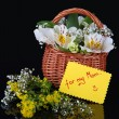 Bouquet of flowers in basket isolated on black - Stockfoto