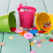 Stock Photo: Colorful buttons strewn from buckets on wooden background
