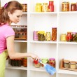 Young housewife cleaning up kitchen on grey background — Stock Photo #23888943