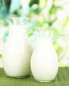 Pitchers of milk on table on bright background — Stock Photo