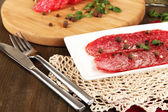 Tasty salami on plate and board on wooden table close-up — Stock Photo