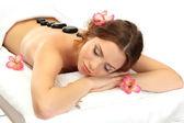 Krásná mladá žena ve spa salonu wellness kameny, izolované na bílém — Stock fotografie