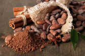 Cocoa beans, cocoa powder and spices on wooden background — Stock Photo