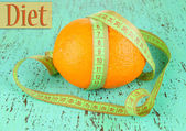 Orange with measuring tape, on color wooden background — Stock Photo