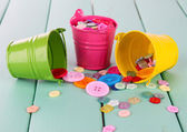 Colorful buttons strewn from buckets on wooden background — Stock Photo