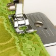 Closeup of sewing machine working part with green cloth — Stock Photo #23928957