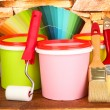 Set for painting: paint pots, brushes, paint-roller, palette of colors on stone wall background — Stock Photo #23929427